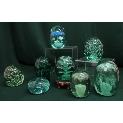 72 - Green coloured glass paperweights including bubble and floral inclusions (8)...