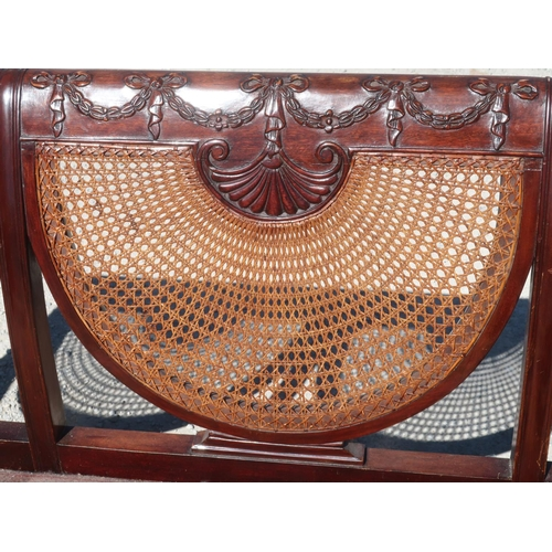 1319 - Geo.III style Bergere sofa, with ribbon tied back rail above three cane panels, double cane arms on ...