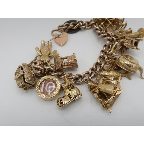 1143 - 9ct gold hallmarked charm bracelet hung with eighteen various charms including treasure chest, artic...