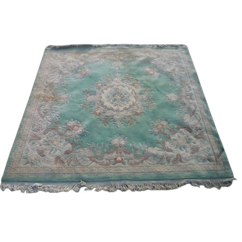 1327 - Chinese embossed woollen rug, green ground central floral medallion and floral pattern border L250cm...