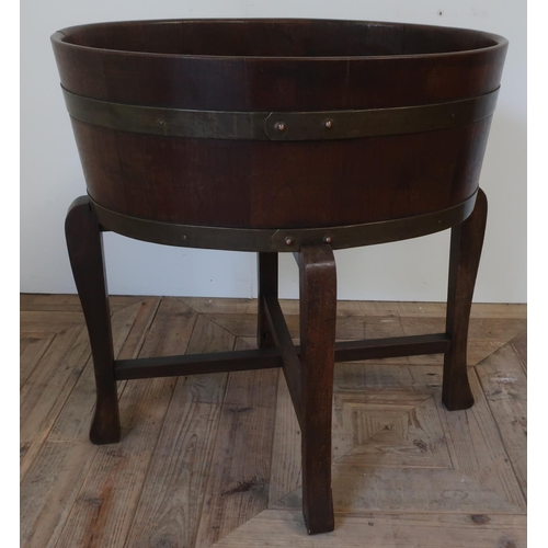 1306 - Edwardian coopered mahogany oval jardiniere, with two brass bands and tin liner, on four angular sup...