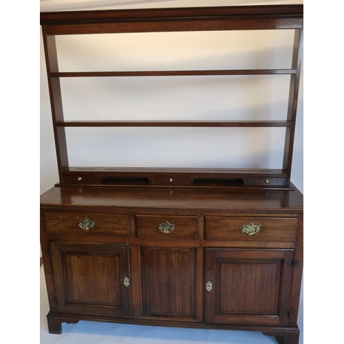 1331 - Geo.III oak dresser, three drawers above a pair of fielded panel doors, with panelled sides on shape...