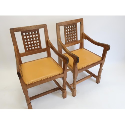 1000 - Robert Mouseman Thompson - a pair of oak elbow chairs with lattice carved backs and brass nail uphol...