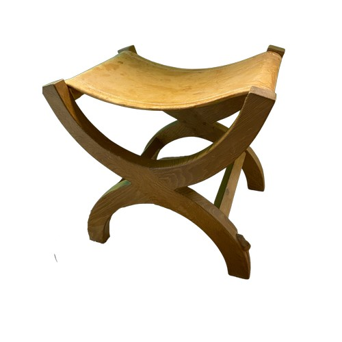 1003 - Robert Mouseman Thompson - an oak stool with stitched slung leather seat on X framed curved supports...