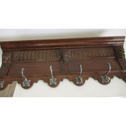 394 - Oak coat rack with arcaded frieze carved with lion mask above six scroll hooks W110cm H39cm