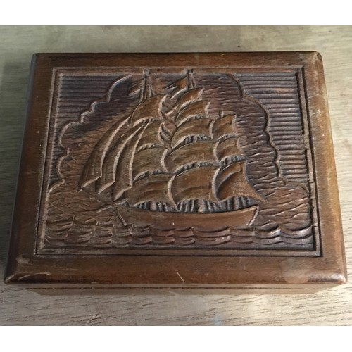478 - Wooden box with a carved design to the lid depicting a ship at sea, containing a quantity of pre-dec...
