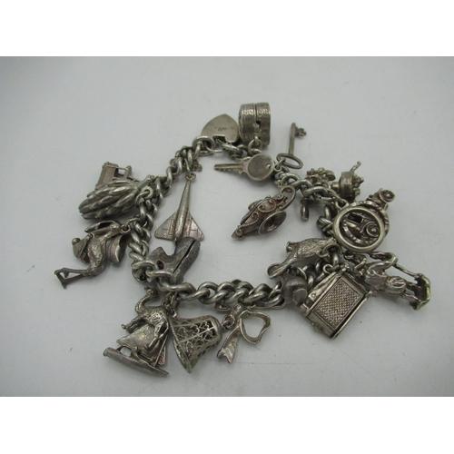 30 - Sterling silver charm bracelet including car, bell keys, bananas, telephone etc stamped 925 2.47ozt