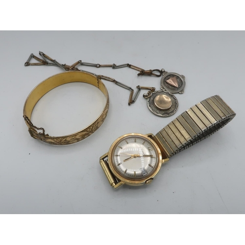 311 - A gold cured hinged gate bracelet with bright cut decoration, two silver fobs, one on chain and a ti...