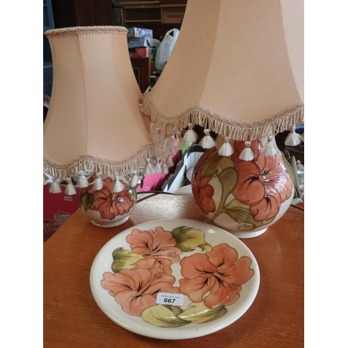 667 - Graduated pair of Moorcroft baluster shaped table lamps decorated with anemone on a white ground H57...