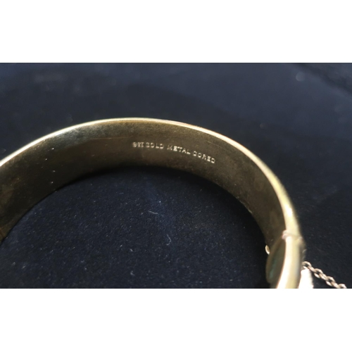 21 - Rolled gold hinged bangle with safety chain stamped 25.3g gross