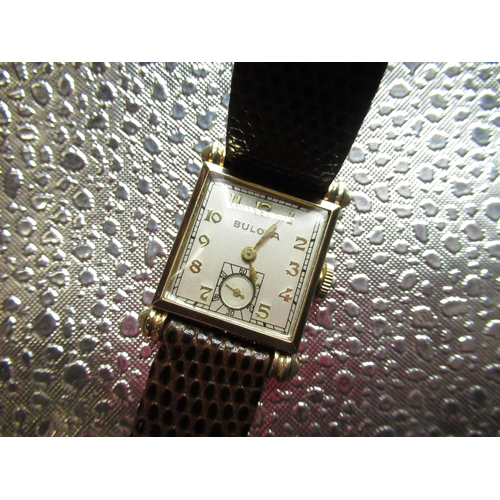 113 - 1940's Bulova hand wound wristwatch. Square 10K rolled gold case with teardrop style lugs on brown l...