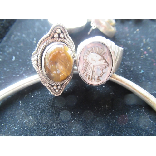29 - Sterling silver ring with tiger eye stone to center Size O, another carved abalone in relief of a Gr...