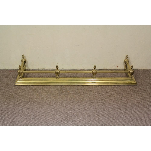 10 - A Brass Fire Fender. The fire fender having six urn finials connected by ribbed tubular rails, appro...