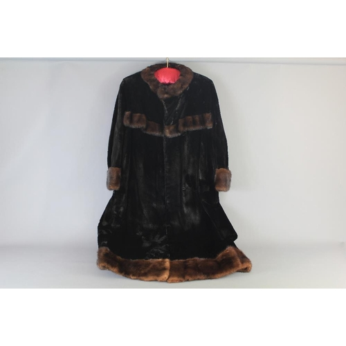 5 - A Vintage Sheared Black Mink Coat. The coat beautifully cut and finished with brown mink trim, appro...