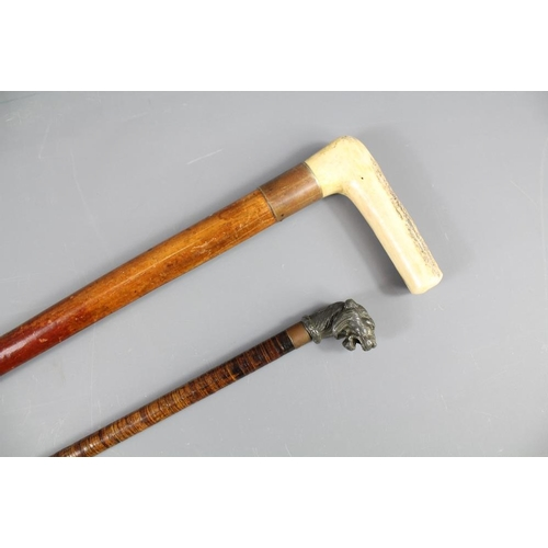 59 - Two Antique Walking Sticks. The first having a pewter tiger-head grip, with bamboo staff approx 84 c...