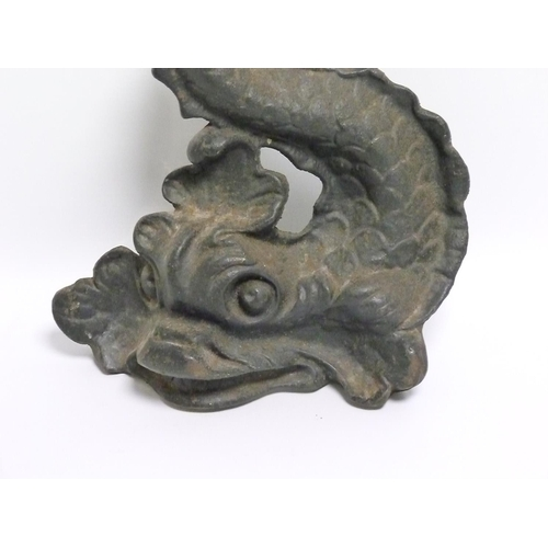 16 - Black painted cast iron doorstop in the form of a classical scrolling dolphin, 34cm high....