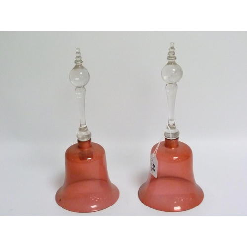 44 - Two cranberry glass hand bells (both lacking clappers), the clear glass handles with ball knop finia...