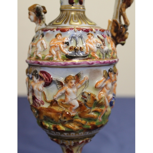 46 - Pair of Capodimonte ewers profusely decorated with moulded classical scenes of revelry, with cherubs...