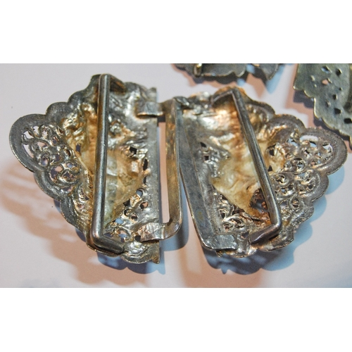 23 - Two Burmese embossed silver buckles, part, and a silver charm bracelet....