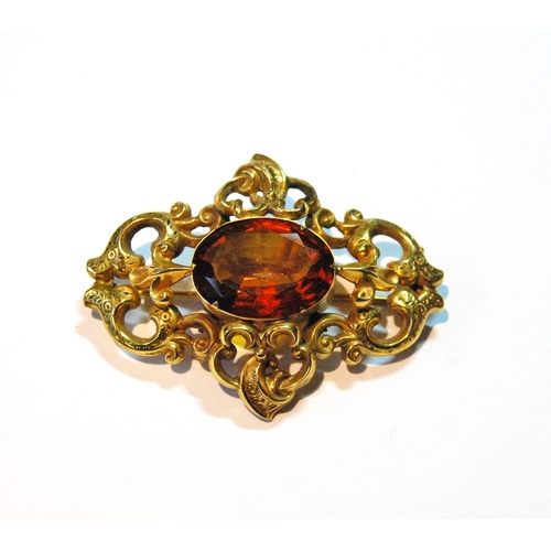 28 - Victorian gold brooch with cairngorm on pierced and engraved scrolls, 14g gross....