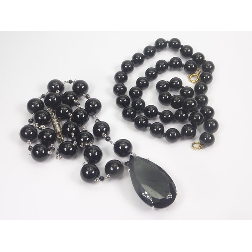 30 - Onyx bead necklace with gold mounted faceted pear shaped drop and another. (2)....