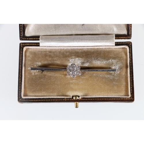 17 - Yellow metal bar brooch set with seven round cut diamond arranged as a flower head, 5.1g gross...
