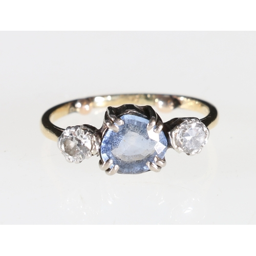 40 - A contemporary three stone ring with two diamonds flanking a pale blue stone, possibly a sapphire, t...