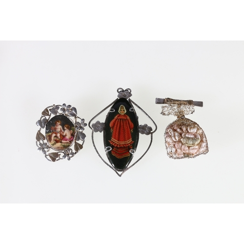 45 - A Russian painted and silver brooch by Lola Lena, a cherub brooch within a floral frame and a ribbon...