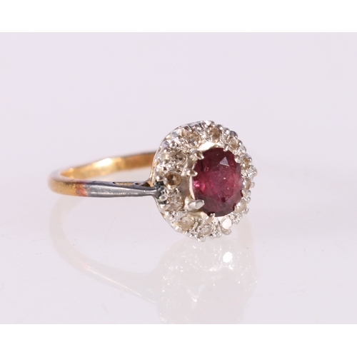 56 - 18ct yellow gold diamond and ruby cluster ring, the central faceted ruby encircled by twelve round d...