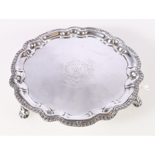 50A - George II silver salver or waiter with feathered pie crust border rim raised on three hoof feet by P...