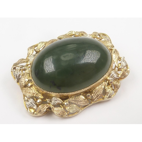 40 - Victorian two colour gold oval brooch with cabochon bloodstone within leafage....