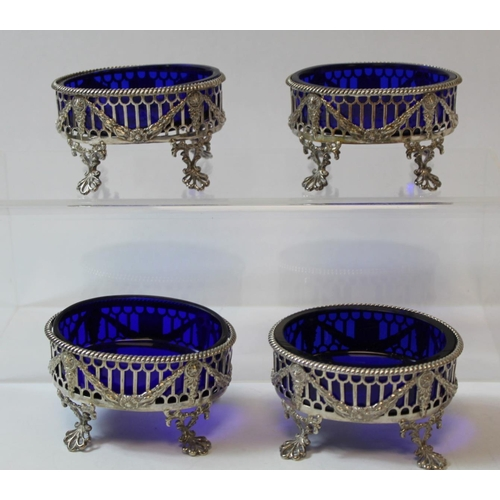 50 - Set of four silver oval salts, pierced with applied embossed swags upon openwork spreading feet, cre...