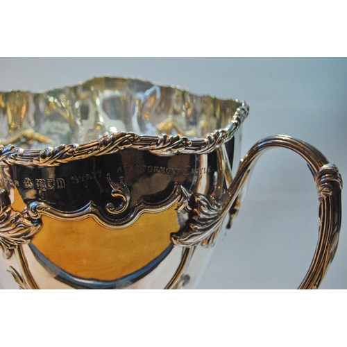 15A - Silver vase of cornucopia form with embossed trails of leafage upon triple foliate supports and scal...