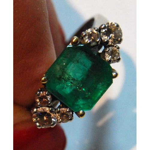 45A - Emerald ring, approximately 8.5mm square, flanked by six diamond brilliants in two sizes, yellow and...
