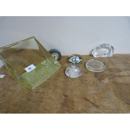 42 - Five glass paperweights, also large glass wedge.