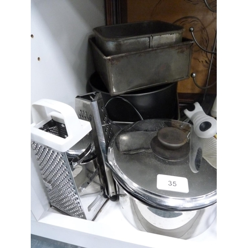 35 - Assorted kitchenware including pans, graters, plates, mug tree, and tins etc....