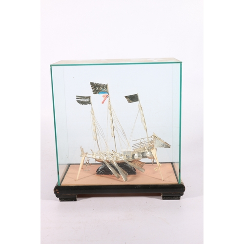 11 - Early 20th Century silver metal junk with eight oars, oarsmen and rigging within a glazed box with b...