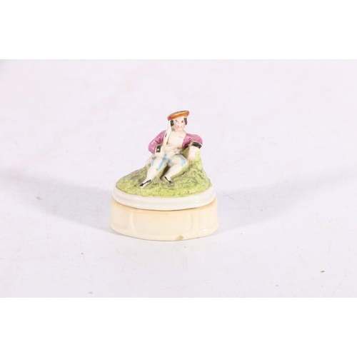 34 - Continental porcelain box and cover with figural finial, 6.5cm tall