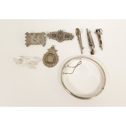 24 - Silver brooch modelled as a gate, five others, a silver medal and a bangle....