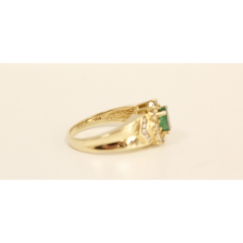 30 - Diamond and emerald ring with an oval cluster flanked by brilliant set chevrons '14k'. Size 'N'.&nbs...