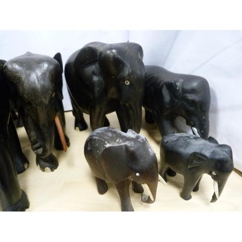 10 - Assorted graduated ebonised elephants.