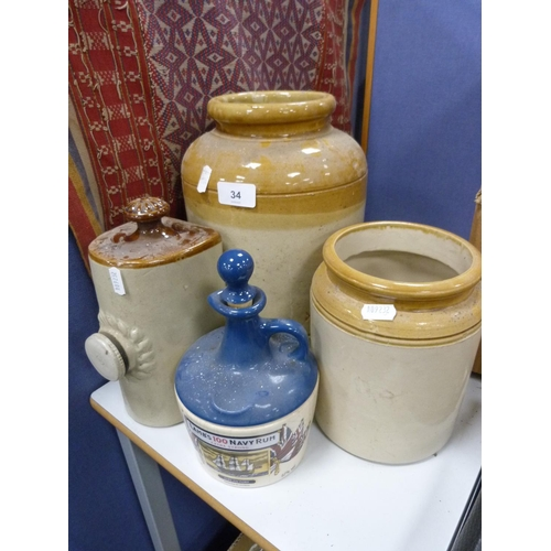 34 - Two earthenware jars, hot water bottle and a Lamb's 100 Navy Rum bottle. (4)