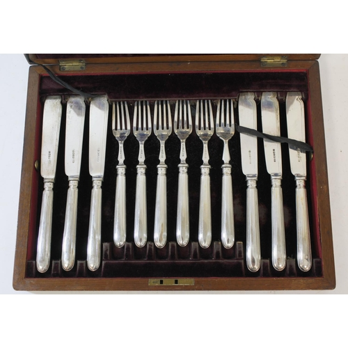 55 - Set of twelve silver fish knives and twelve forks with oval reeded handles by Harrison Brothers, She...