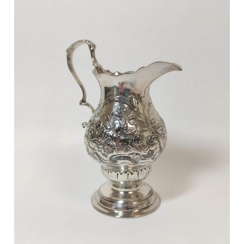 43 - Silver cream jug of baluster shape, crested, with embossed flowers and scrolls upon circular moulded...