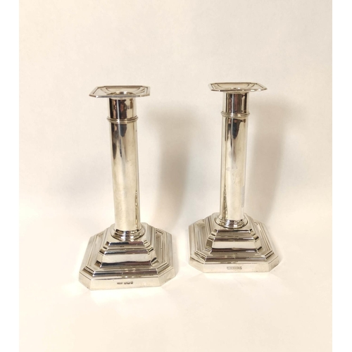 8 - Pair of silver table candlesticks with plain cylindrical stems on stepped bases, Sheffield 1908, 16c...