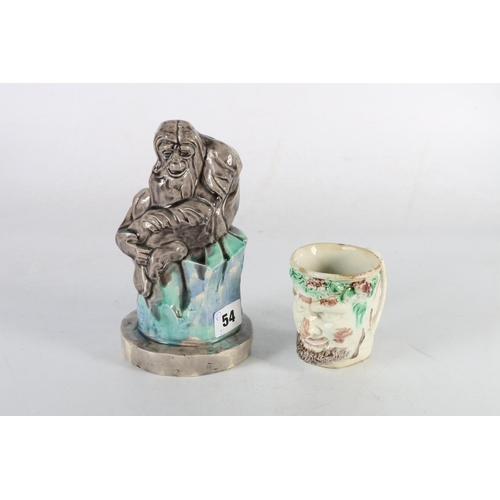 54 - Ceramic model of an orangutan seated on a rock and a mug in the form of a face