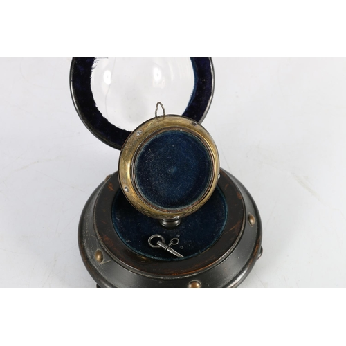 55 - Early 20th century pocket-watch holder under hinged glass dome, 13cm, (A/F)