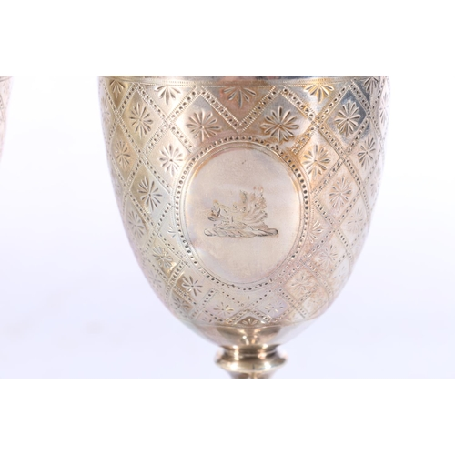 5 - A pair of Victorian silver goblets with allover incised decoration, the cartouches with boars head i...