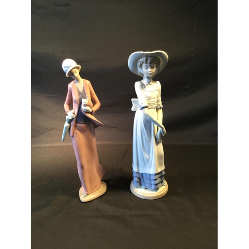 23 - 2 x Nao lady figurines. Both approx 31 cm in height. Slight chip to end of umbrella....