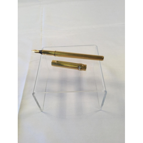 37 - CARTIER; a Must de Cartier gold plated fountain pen with ribbed body. 696977 stamped to the base of ...